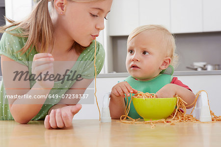 Girl and toddler playing with spaghetti Stock Photo - Premium Royalty-Free, Image code: 649-07238337