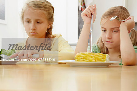 Girls poking vegetables on plate Stock Photo - Premium Royalty-Free, Image code: 649-07238340