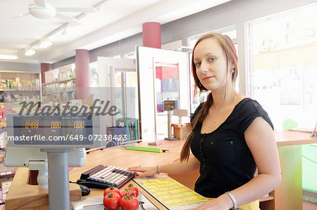 Woman working in organic food market, serving at cash register Stock Photo - Premium Royalty-Free, Image code: 649-07238423