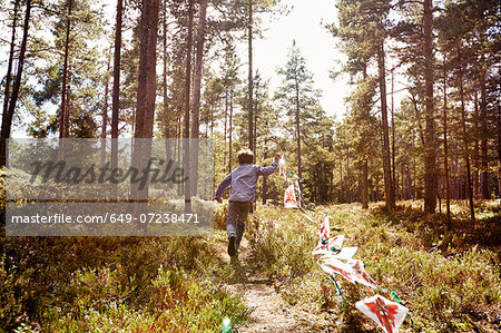 Boy running through forest pulling bunting Stock Photo - Premium Royalty-Free, Image code: 649-07238471