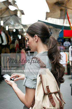 Young woman texting on cell phone, San Lorenzo market, Florence, Tuscany, Italy Stock Photo - Premium Royalty-Free, Image code: 649-07238567