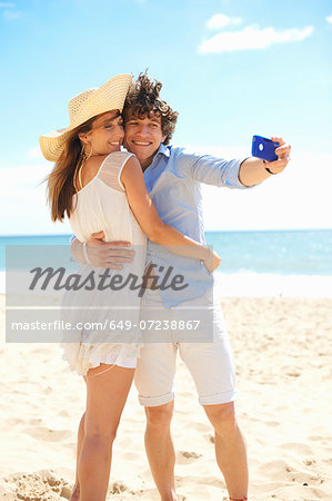 Couple self photographing with mobile phone on beach Stock Photo - Premium Royalty-Free, Image code: 649-07238867