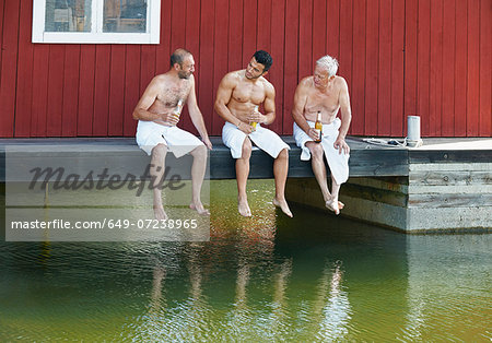 Three male friends sharing a beer outside sauna Stock Photo - Premium Royalty-Free, Image code: 649-07238965
