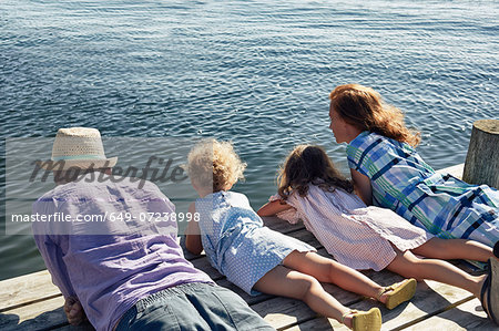 Parents and daughters lying on pier, Utvalnas, Gavle, Sweden Stock Photo - Premium Royalty-Free, Image code: 649-07238998