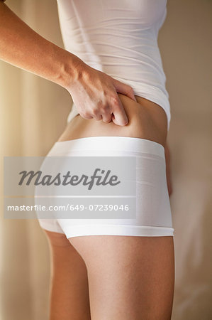 Close up of young woman grabbing skin on hip Stock Photo - Premium Royalty-Free, Image code: 649-07239046