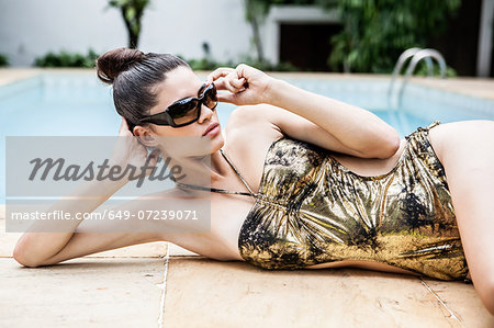 Young woman in gold bathing costume at hotel poolside Stock Photo - Premium Royalty-Free, Image code: 649-07239071