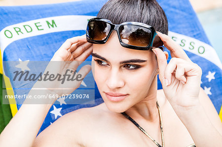 Close up portrait of young woman holding sunglasses Stock Photo - Premium Royalty-Free, Image code: 649-07239074