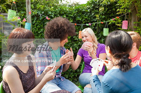Group of young adult friends playing cards in garden Stock Photo - Premium Royalty-Free, Image code: 649-07239144