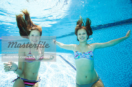 Two teenage girls swimming underwater in swimming pool Stock Photo - Premium Royalty-Free, Image code: 649-07239174