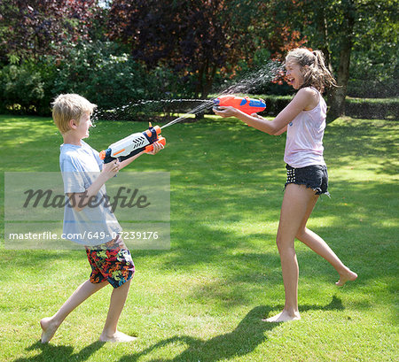 Brother and sister play fighting with water guns in garden Stock Photo - Premium Royalty-Free, Image code: 649-07239176