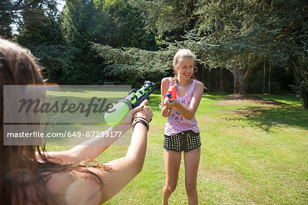 Two teenage girls firing water guns in garden Stock Photo - Premium Royalty-Free, Image code: 649-07239177