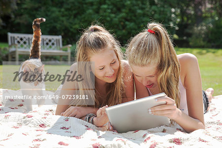 Two teenage girls on picnic blanket looking at digital tablet Stock Photo - Premium Royalty-Free, Image code: 649-07239181
