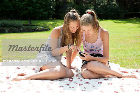 Two teenage girls on picnic blanket looking at mobile phone Stock Photo - Premium Royalty-Free, Image code: 649-07239182