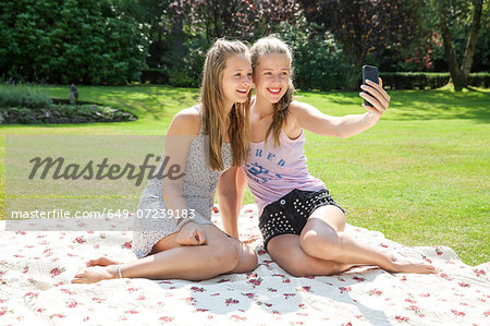 Two teenage girls on picnic blanket taking self portrait Stock Photo - Premium Royalty-Free, Image code: 649-07239183
