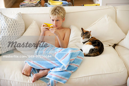 Boy sitting on sofa playing handheld game Stock Photo - Premium Royalty-Free, Image code: 649-07239184