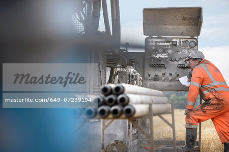 Drilling rig worker inspecting machinery Stock Photo - Premium Royalty-Free, Image code: 649-07239194