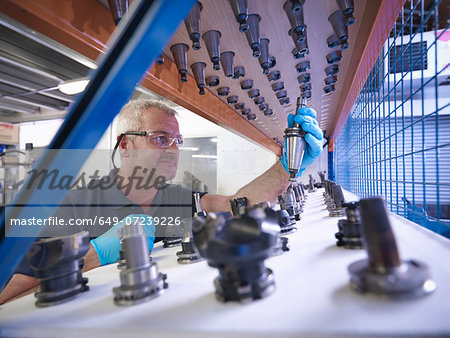 Engineer selecting lathe cutting tools in factory Stock Photo - Premium Royalty-Free, Image code: 649-07239226