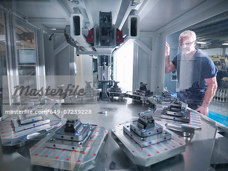 Engineer inspecting automatic lathe in factory Stock Photo - Premium Royalty-Free, Image code: 649-07239228