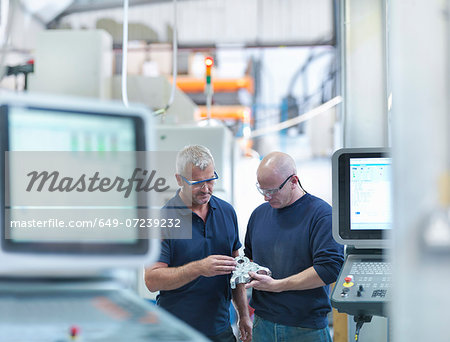 Engineers inspecting complex metal component in factory Stock Photo - Premium Royalty-Free, Image code: 649-07239232