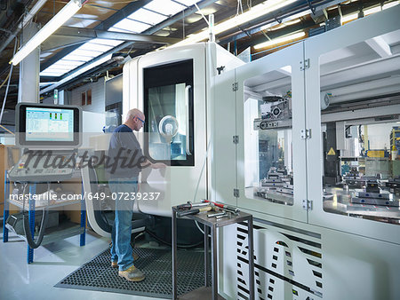 Engineer at computer numerical controlled lathe (CNC) in factory Stock Photo - Premium Royalty-Free, Image code: 649-07239237