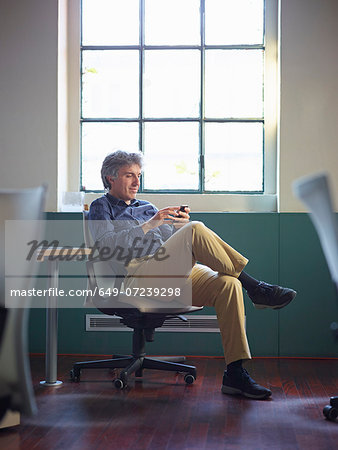 Mature businessman sitting on office chair wit cell phone Stock Photo - Premium Royalty-Free, Image code: 649-07239298