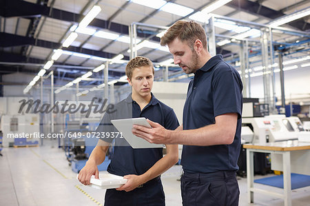 Workers checking order in engineering factory Stock Photo - Premium Royalty-Free, Image code: 649-07239371