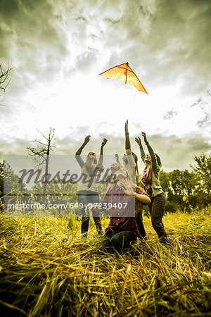 Five young women flying kite in scrubland Stock Photo - Premium Royalty-Free, Image code: 649-07239407