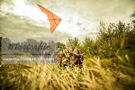 Five young women having fun with kite in scrubland Stock Photo - Premium Royalty-Free, Image code: 649-07239408