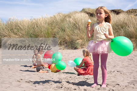 Girl holding balloon eating ice cream on beach, Wales, UK Stock Photo - Premium Royalty-Free, Image code: 649-07239464