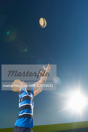 Young man catching rugby ball Stock Photo - Premium Royalty-Free, Image code: 649-07239531