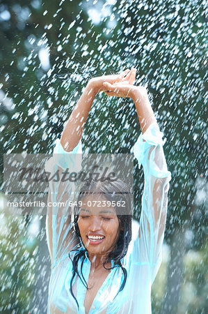 Portrait of young woman in rain with arms raised Stock Photo - Premium Royalty-Free, Image code: 649-07239562