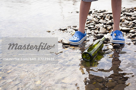 Boy standing by message in a bottle at seaside Stock Photo - Premium Royalty-Free, Image code: 649-07239616