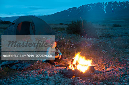 Woman sitting at campfire, Eyjafjordur, North Iceland Stock Photo - Premium Royalty-Free, Image code: 649-07239668