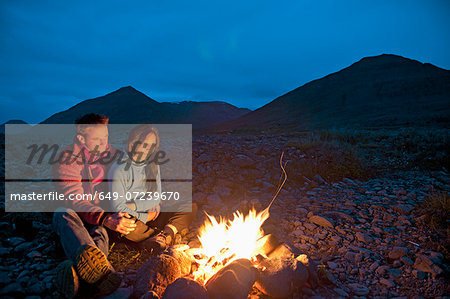 Couple sitting at campfire, Eyjafjordur, North Iceland Stock Photo - Premium Royalty-Free, Image code: 649-07239670