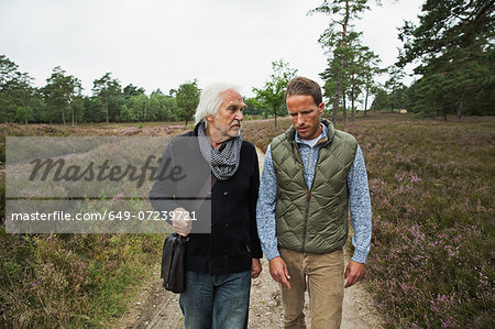 Father and adult son walking on dirt track Stock Photo - Premium Royalty-Free, Image code: 649-07239721