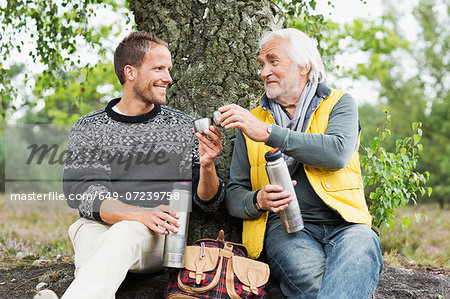Father and adult son drinking coffee from flask Stock Photo - Premium Royalty-Free, Image code: 649-07239758