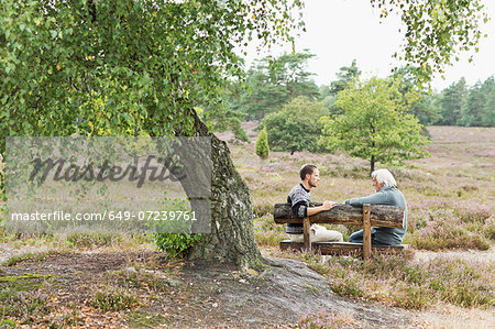 Senior man and mid adult man sitting on bench Stock Photo - Premium Royalty-Free, Image code: 649-07239761