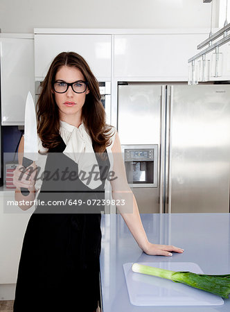 Young woman holding carving knife in kitchen Stock Photo - Premium Royalty-Free, Image code: 649-07239823