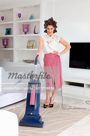 Young woman vacuuming living room Stock Photo - Premium Royalty-Free, Image code: 649-07239834