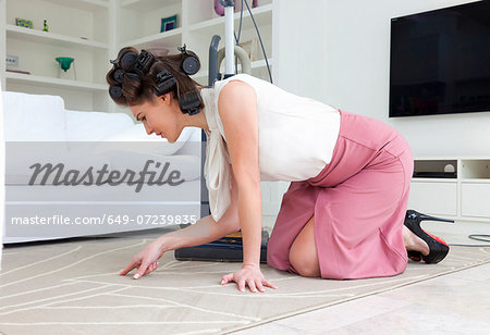 Young woman on hands and knees inspecting rug Stock Photo - Premium Royalty-Free, Image code: 649-07239835