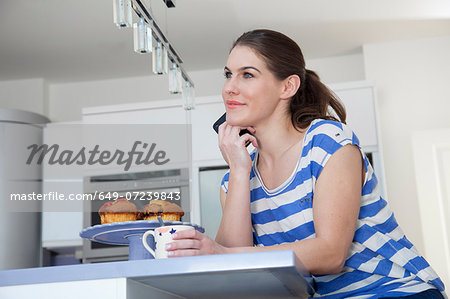 Young woman at breakfast bar with coffee and cell phone Stock Photo - Premium Royalty-Free, Image code: 649-07239843
