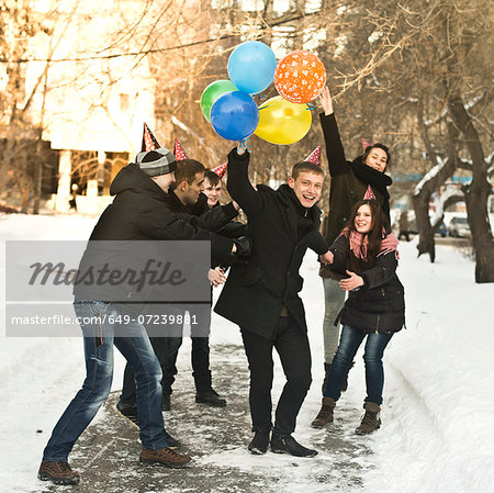 Group of young friends with party hats and balloons Stock Photo - Premium Royalty-Free, Image code: 649-07239881