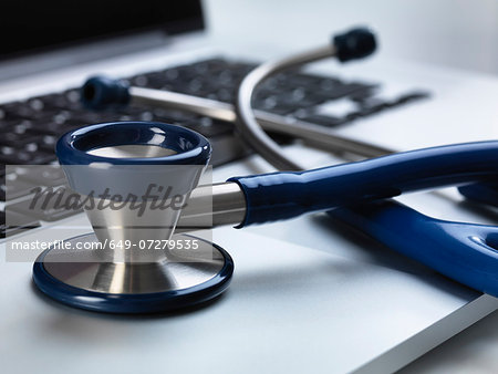 Stethoscope sitting on laptop illustrating online healthcare and doctor's desk Stock Photo - Premium Royalty-Free, Image code: 649-07279535