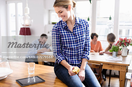 Young woman eating apple looking at tablet screen smiling, people in background Stock Photo - Premium Royalty-Free, Image code: 649-07279568