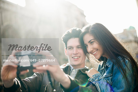 Young couple photographing themselves Stock Photo - Premium Royalty-Free, Image code: 649-07279664