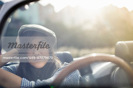Young woman wearing flat cap in convertible