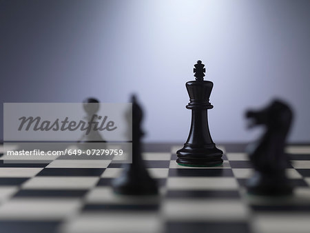 Chess pieces on a board showing king Stock Photo - Premium Royalty-Free, Image code: 649-07279759