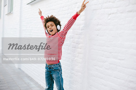 Boy on street with arms out listening to headphones Stock Photo - Premium Royalty-Free, Image code: 649-07280036