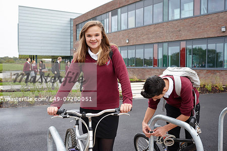 Teenagers unlocking cycles outside school Stock Photo - Premium Royalty-Free, Image code: 649-07280051