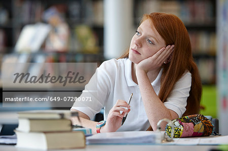 Portrait of teenage girl daydreaming in library Stock Photo - Premium Royalty-Free, Image code: 649-07280071